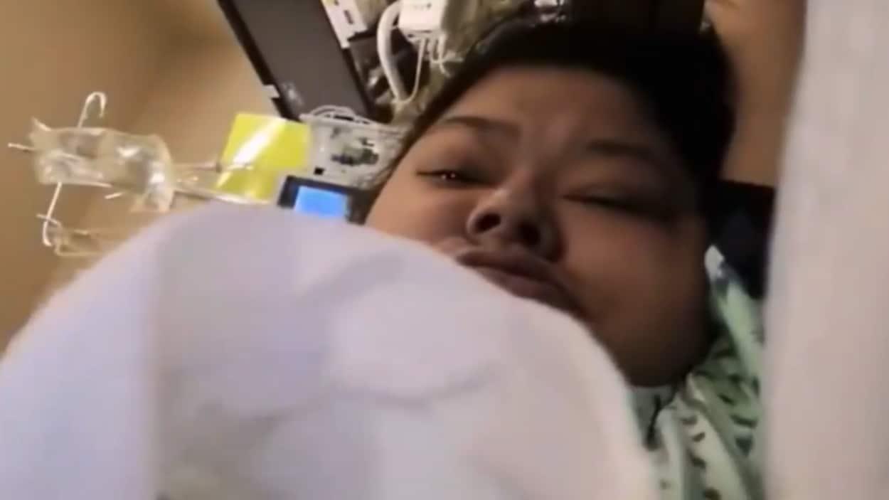 Une femme dans un lit d'hôpital.
