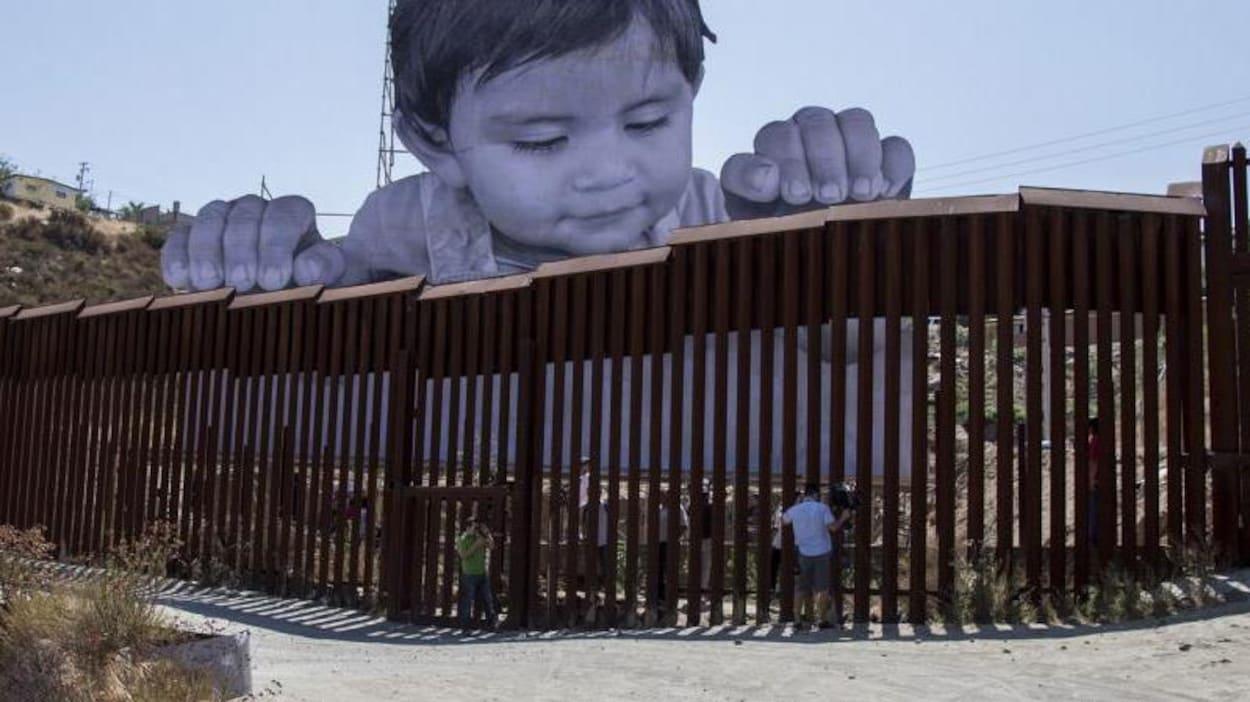 L'enfant a les mains sur le mur.
