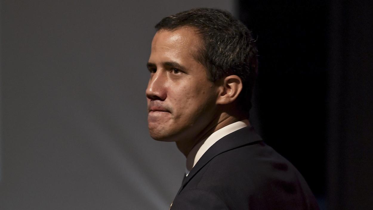 Un homme portant un complet et une cravate photographié de profil.