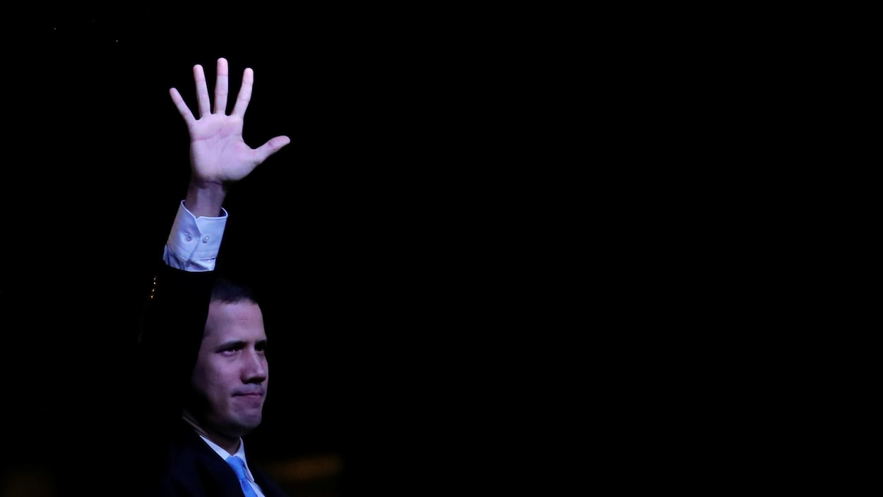 Juand Guaido lève la main lors d'un rassemblement en pleine nuit.