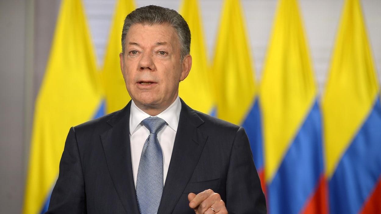 Les cheveux poivre et sel, le président colombien Juan Manuel Santos parle devant des drapeaux colombiens.