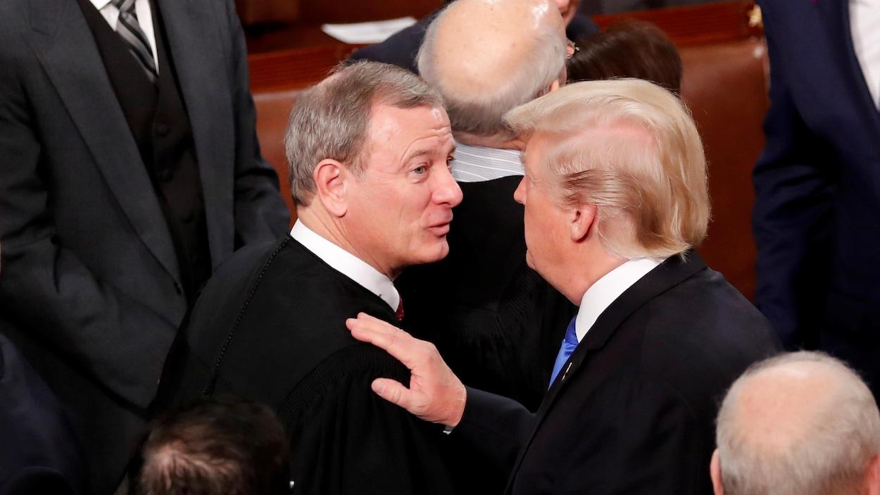 Le président Trump s'entretient avec le juge John Roberts, lui mettant la main sur l'épaule. (archives)