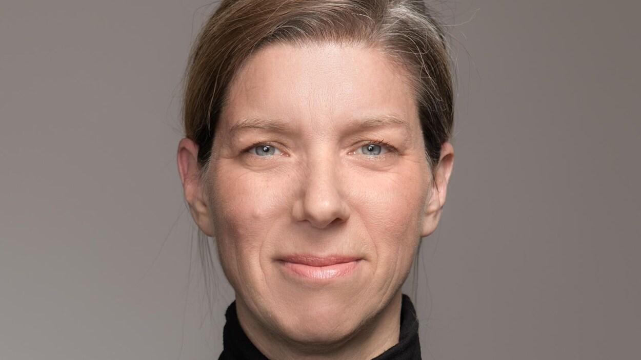 Portrait en couleur, sur fond gris, de l'autrice Julie Bouchard. Elle porte les cheveux attachés et un col roulé noir. Elle sourit légèrement, bouche fermée.