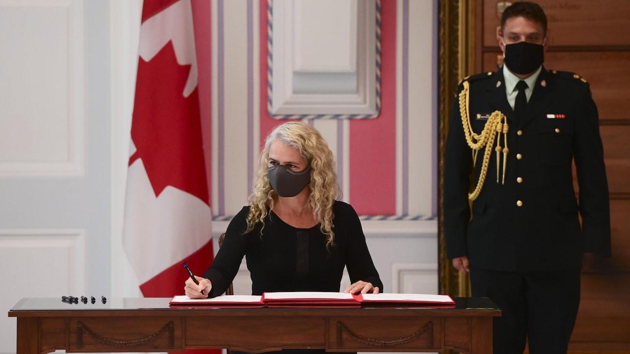 Julie Payette, gouverneure générale du Canada, est assise et signe un document, portant un couvre-visage, devant un drapeau du Canada et un agent en uniforme.