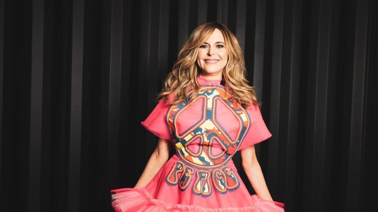 Une femme porte une robe rose sur laquelle apparaît un signe de paix.