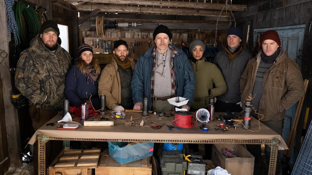 7 personnes habillées de manteaux sont devant une table avec divers objets et elles regardent la caméra.