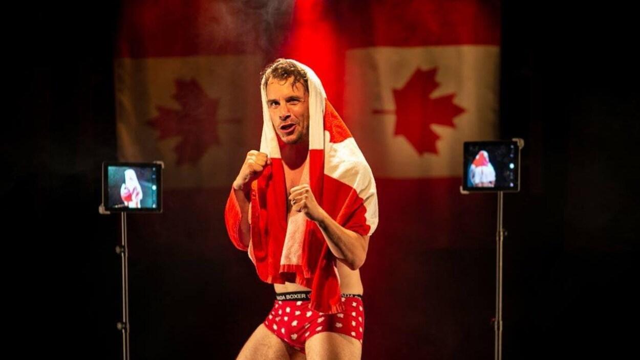 Un homme vêtu de caleçons se tient en position de boxe avec un drapeau canadien sur la tête.