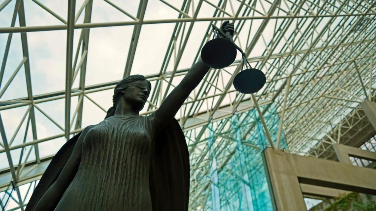 Une statue aux yeux bandés tient une balance sous le toit en verre du palais de justice à Vancouver.
