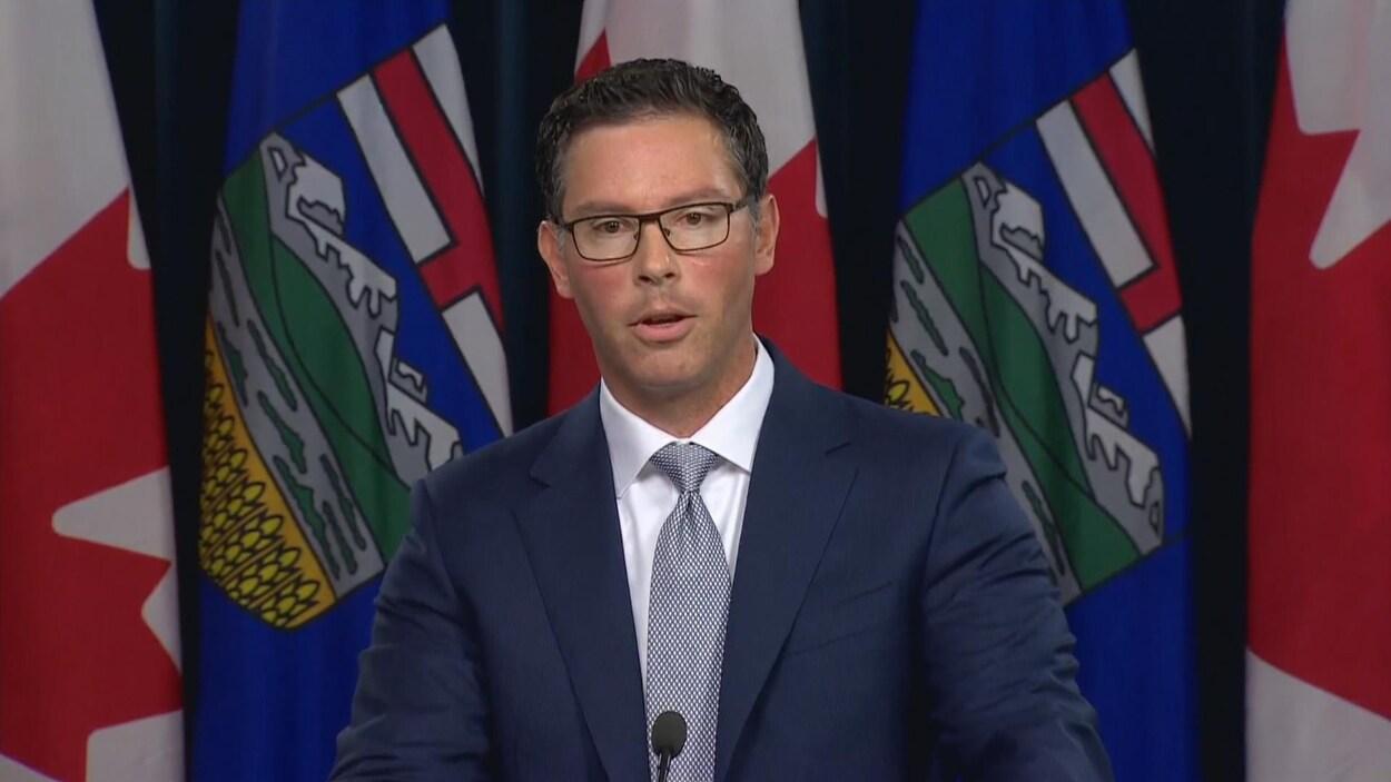 Un homme en costume-cravate parle devant une rangée de drapeaux de l'Alberta et du Canada.