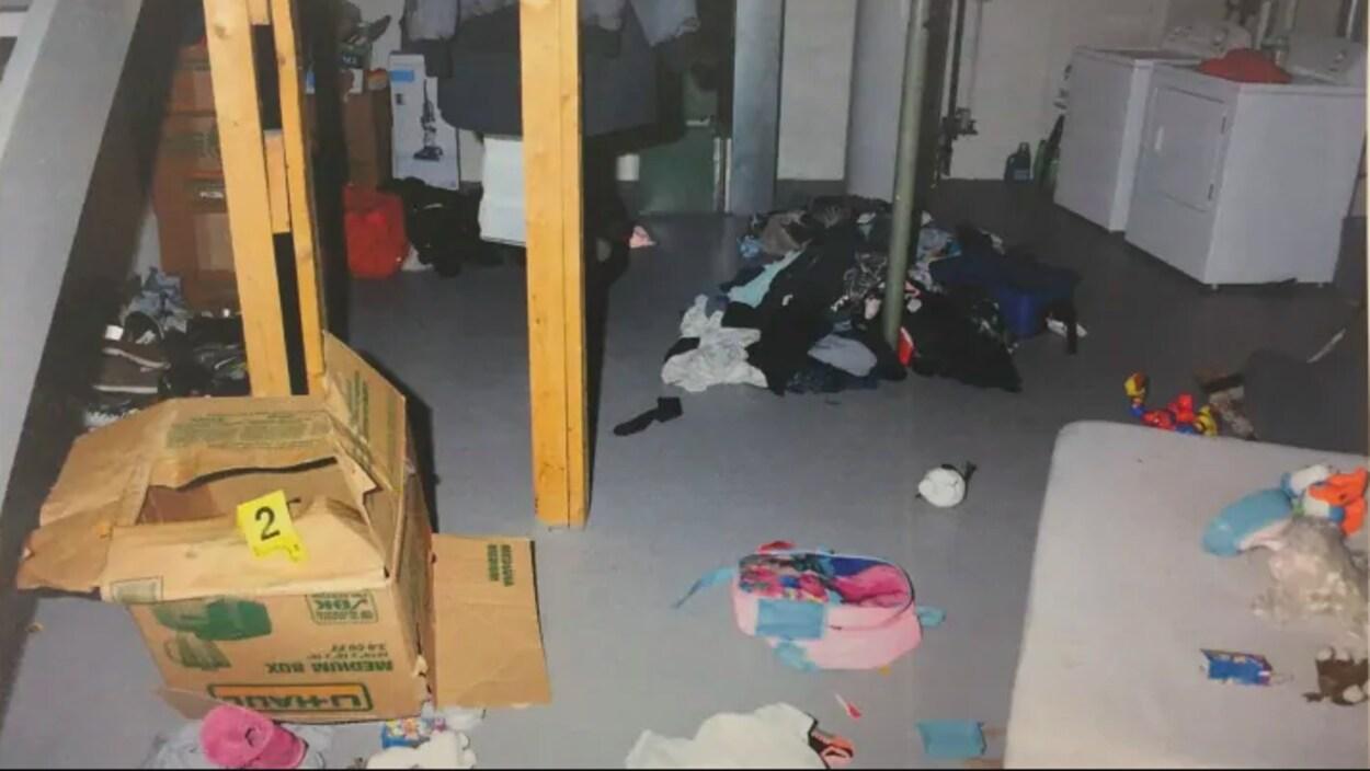 Un sous-sol sombre et encombré de divers objets, dont une boîte de carton vide et un tas de vêtements.
