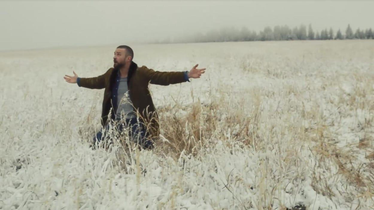 Justin Timberlake est agenouillé dans un champ enneigé, les bras tendus vers le ciel.