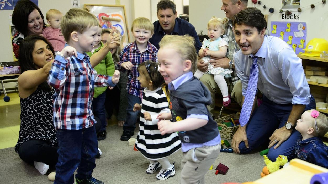 Justin Trudeau est agenouillé devant des enfants, dont certains sont accompagnés par un parent.