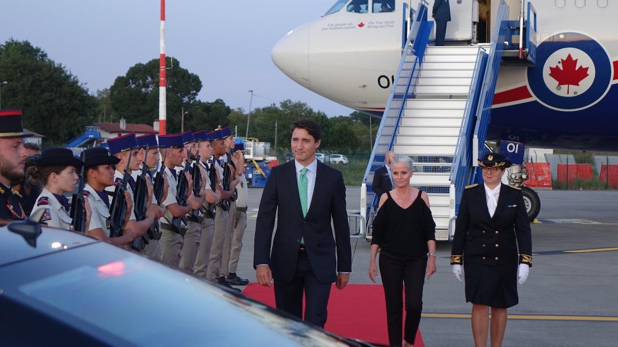 Justin Trudeau marche sur un tapis rouge à sa descente de l'avion.