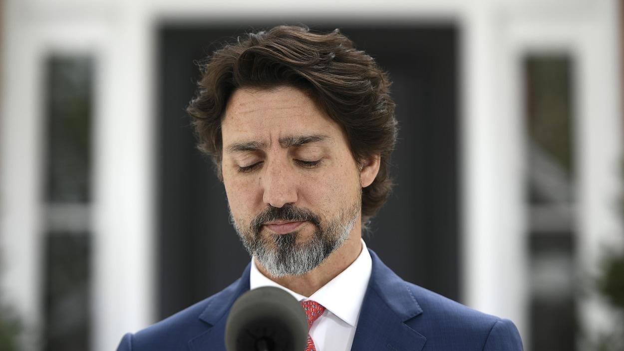 Le premier ministre Justin Trudeau marque une pause en fermant les yeux durant un point de presse.