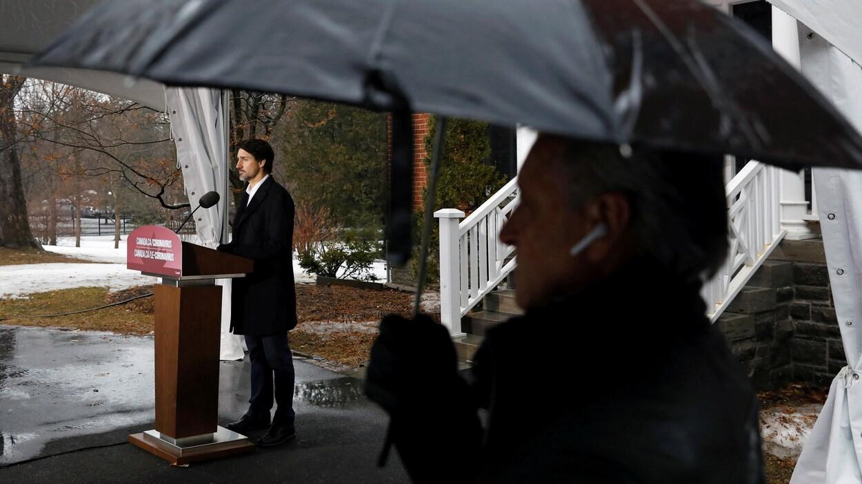 Justin Trudeau en conférence de presse à l'extérieur.