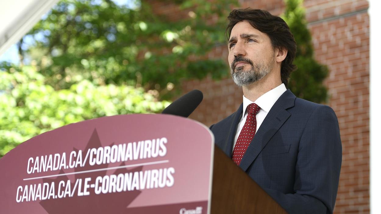 Le premier ministre Justin Trudeau debout derrière son lutrin durant une conférence de presse.