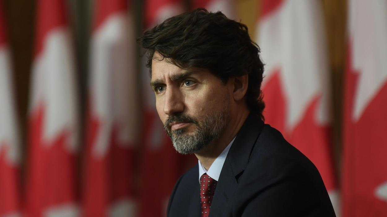 Le premier ministre Justin Trudeau assis devant des drapeaux canadiens durant une conférence de presse.