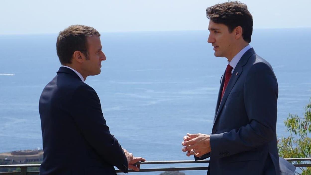Emmanuel Macron et Justin Trudeau se regardent dans les yeux.