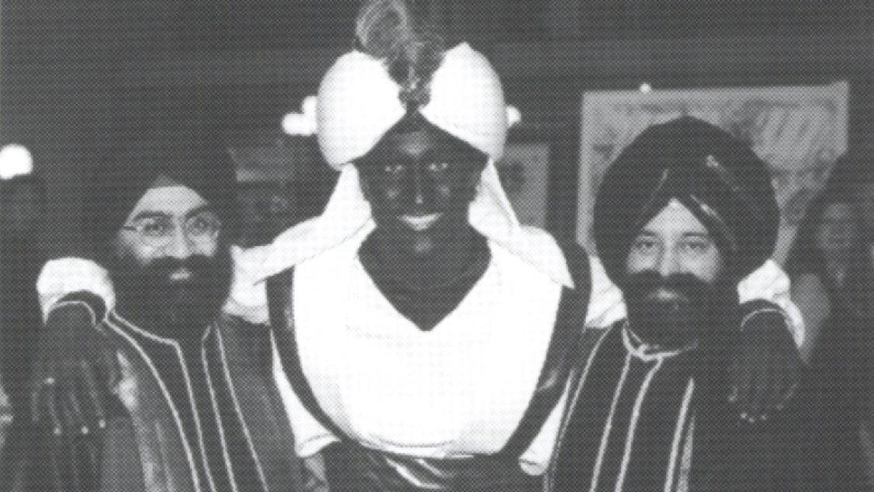 Justin Trudeau, déguisé et le visage maquillé en brun, est photographié au centre de deux autres hommes.