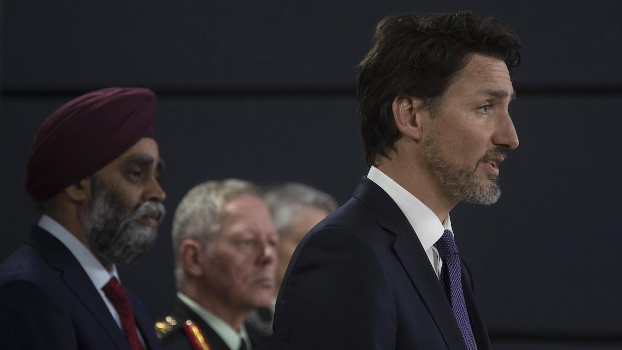 Justin Trudeau s'adresse aux médias. Derrière lui se tiennent le général Jonathan Vance et le ministre de la Défense nationale Harjit Sajjan.