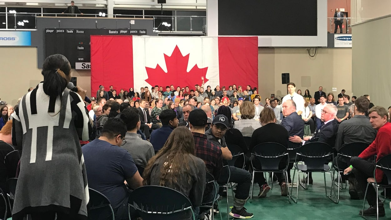 Le premier ministre Justin Trudeau se tient debout au centre de plusieurs personnes assises. Derrière lui se trouve un grand drapeau du Canada.