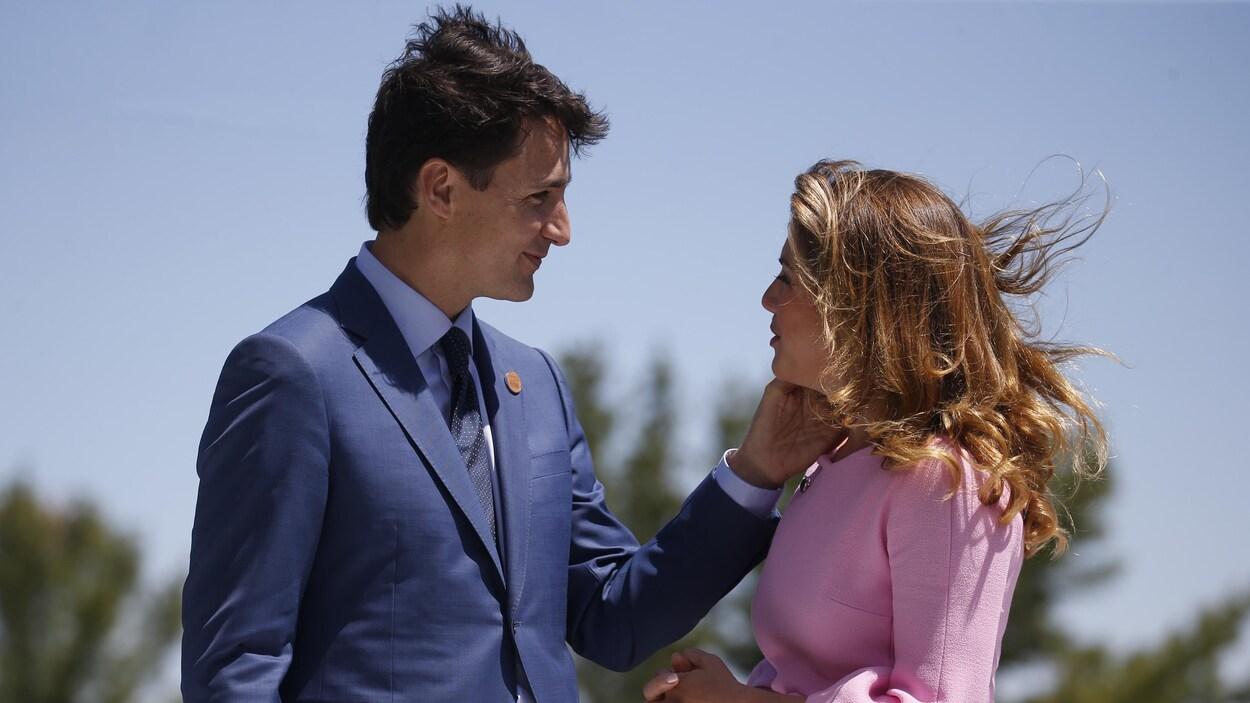 M. Trudeau pose la main gauche sur la joue de sa femme en lui souriant.