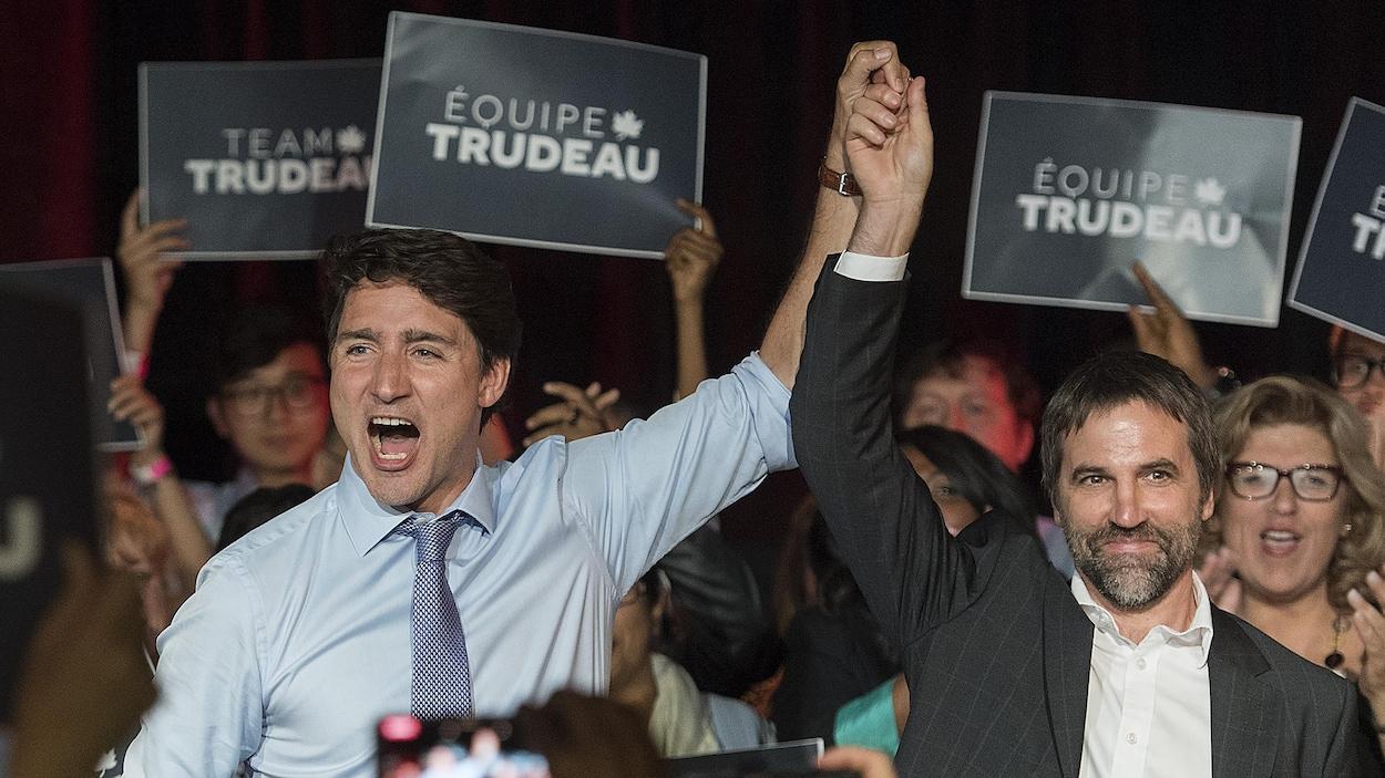 Les deux hommes, sur scène, mains jointes et levées, sont entourés de militants.