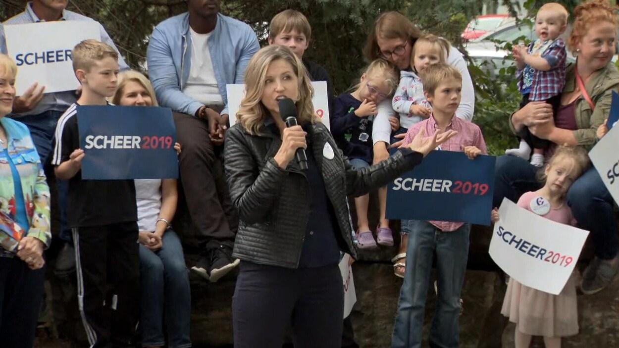 Une femme parle au micro devant une foule de partisans conservateurs. Derrière elle, des enfants tiennent des pancartes où il est écrit « Scheer 2019 ».