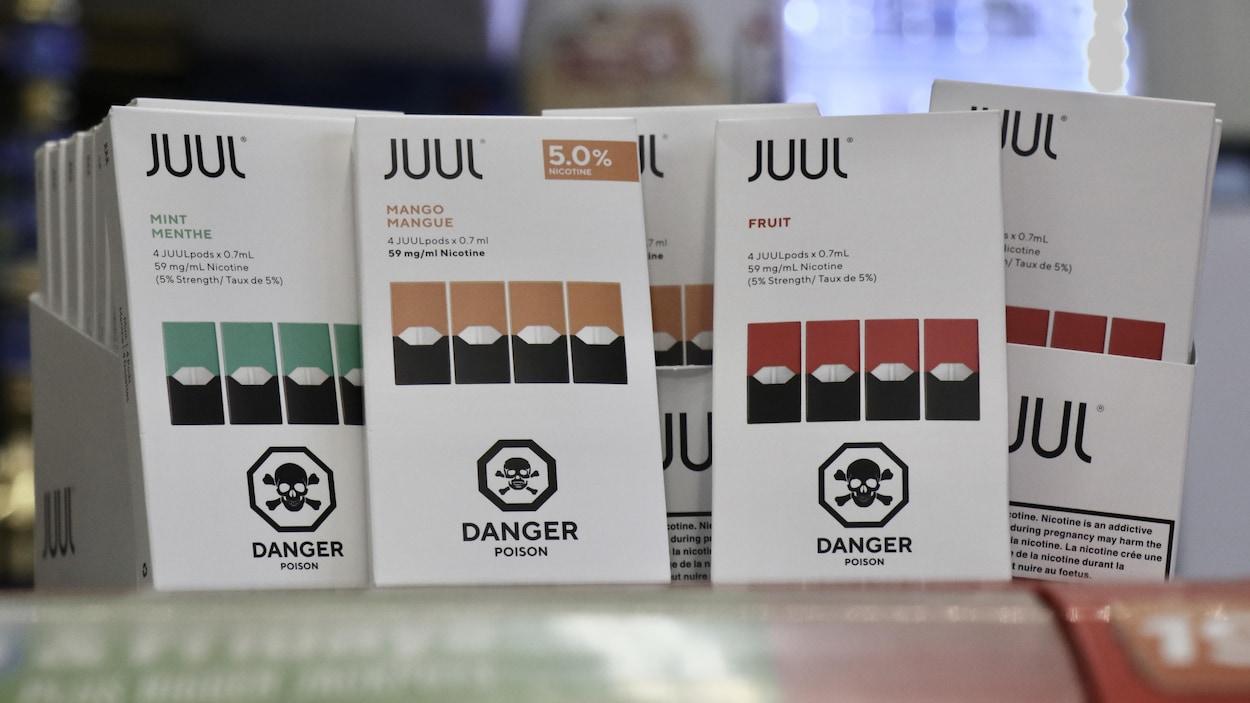 Cinq boîtes de Juul de différentes saveurs sur une étagère.
