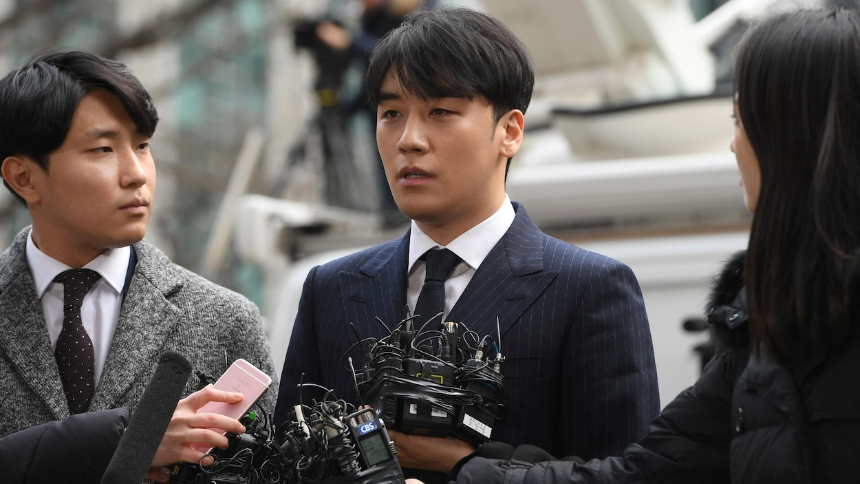 Le chanteur de K-pop, entouré de journalistes, parle face à des micros.
