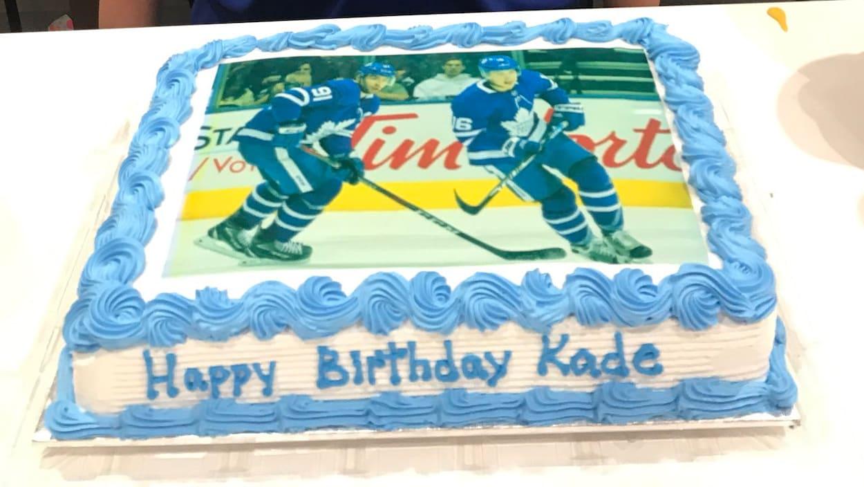 Un jeune garçon brun avec un t-shirt des Maple Leafs et un gâteau avec des joueurs de hockey en photo.