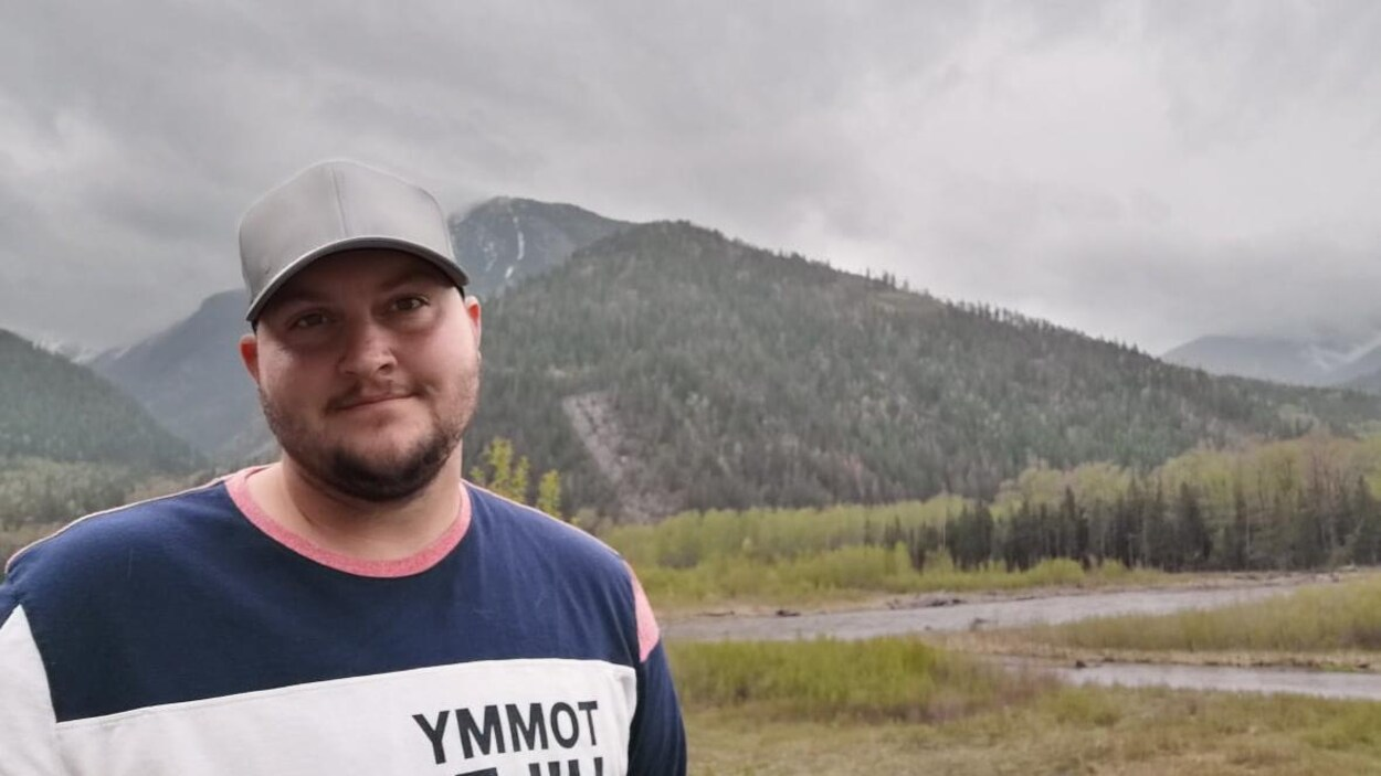 Kaden Webb devant une rivière et une montagne.