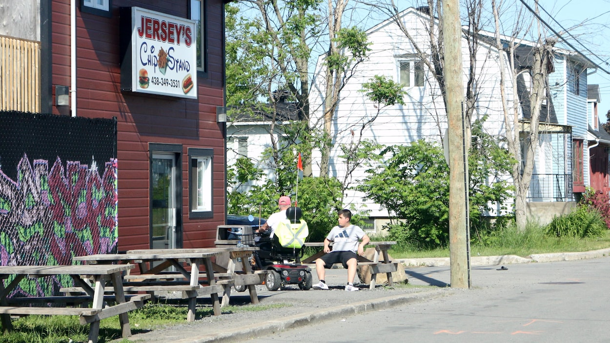 Des clients prennent une pause devant un casse-croûte de la communauté mohawk de Kahnawake, située près de Montréal.
