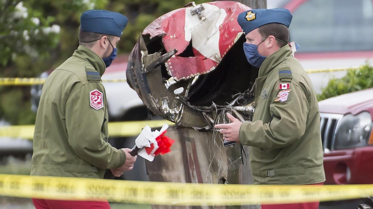 Deux membres des forces armées canadiennes en uniforme devant des débris de l'avion.