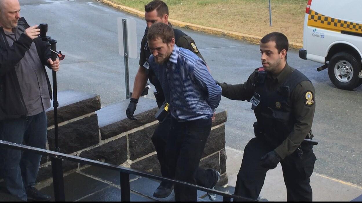 L'accusé entouré de deux policiers de la Sûreté du Québec