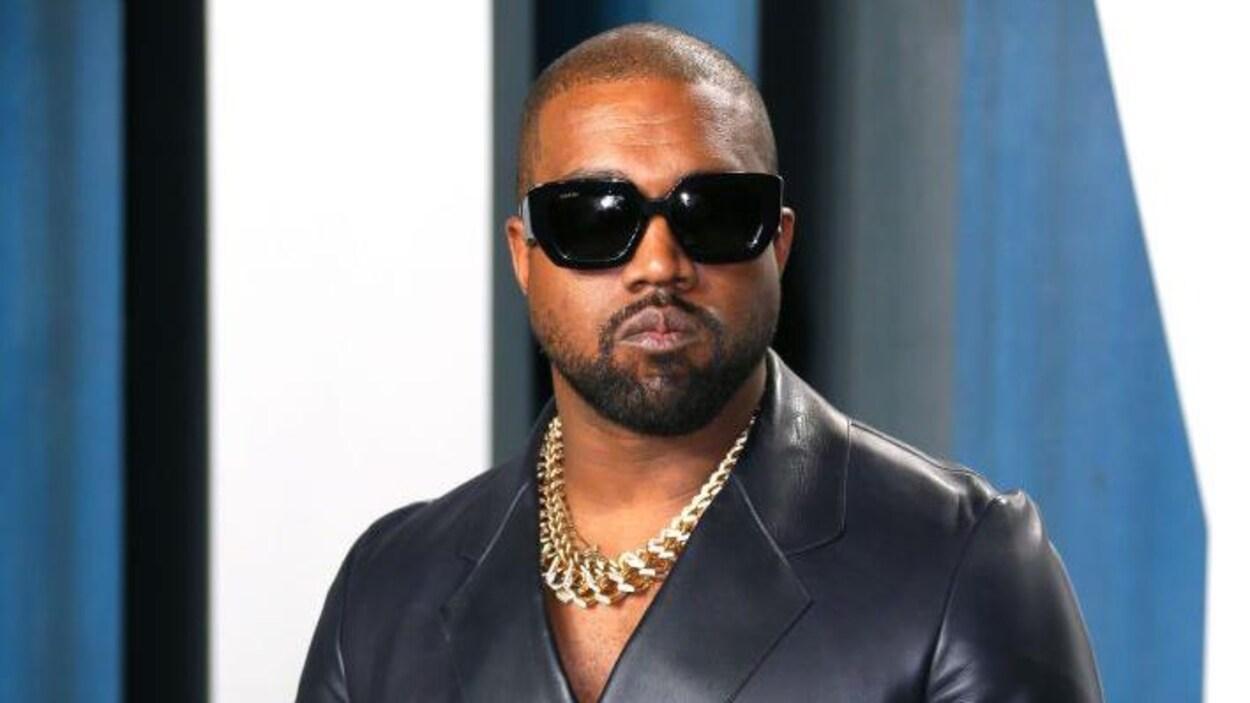 Kanye West porte une veste en cuir et des lunettes de soleil.