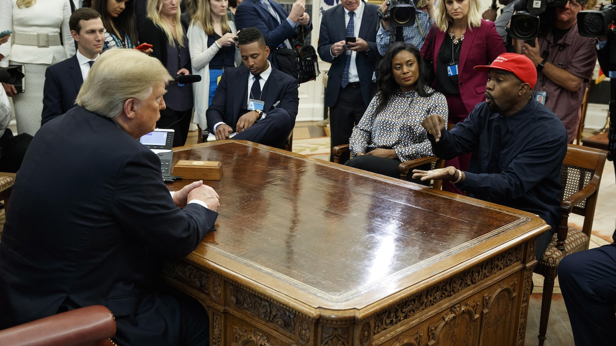 Donald Trump et Kanye West sont assis face à face, entourés de photographes et de journalistes.