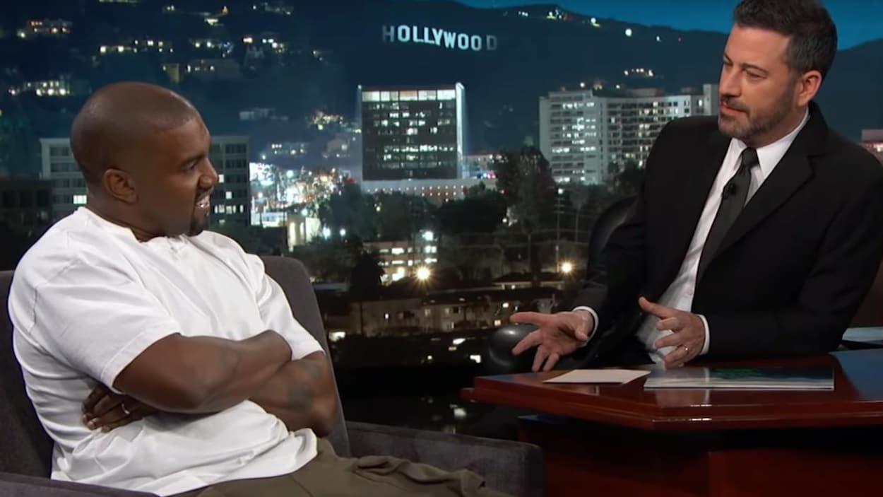 Assis dans un fauteuil, le rappeur Kanye West croise les bras et sourit tandis que l'animateur Jimmy Kimmel, lui aussi assis, lui pose une question.
