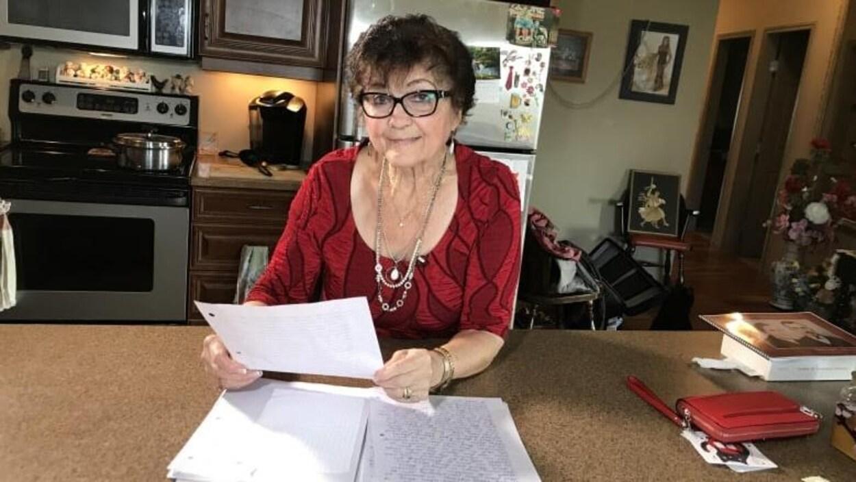 Une femme aînée s'appuie sur un comptoir en tenant la feuille d'un journal.