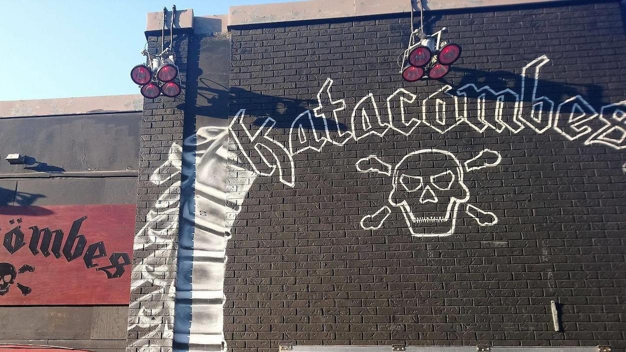 Image d'une façade des Katacombes, où l'on aperçoit le logo de la salle de spectacle peint sur un mur noir.