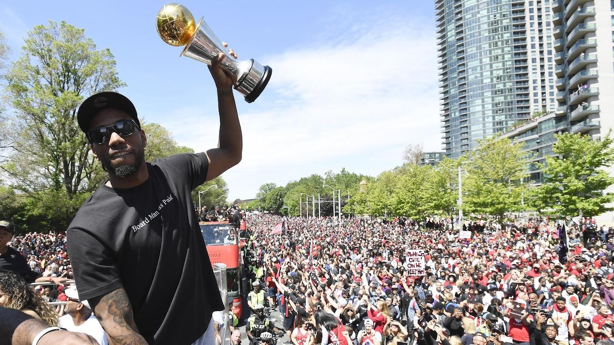 Il brandit le trophée Larry-O'Brien devant la foule qui remplit complètement la rue.