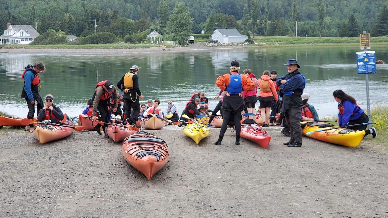 Un groupe de touristes est en train de se préparer à quitter la berge pour aller faire du kayak dans le fleuve.