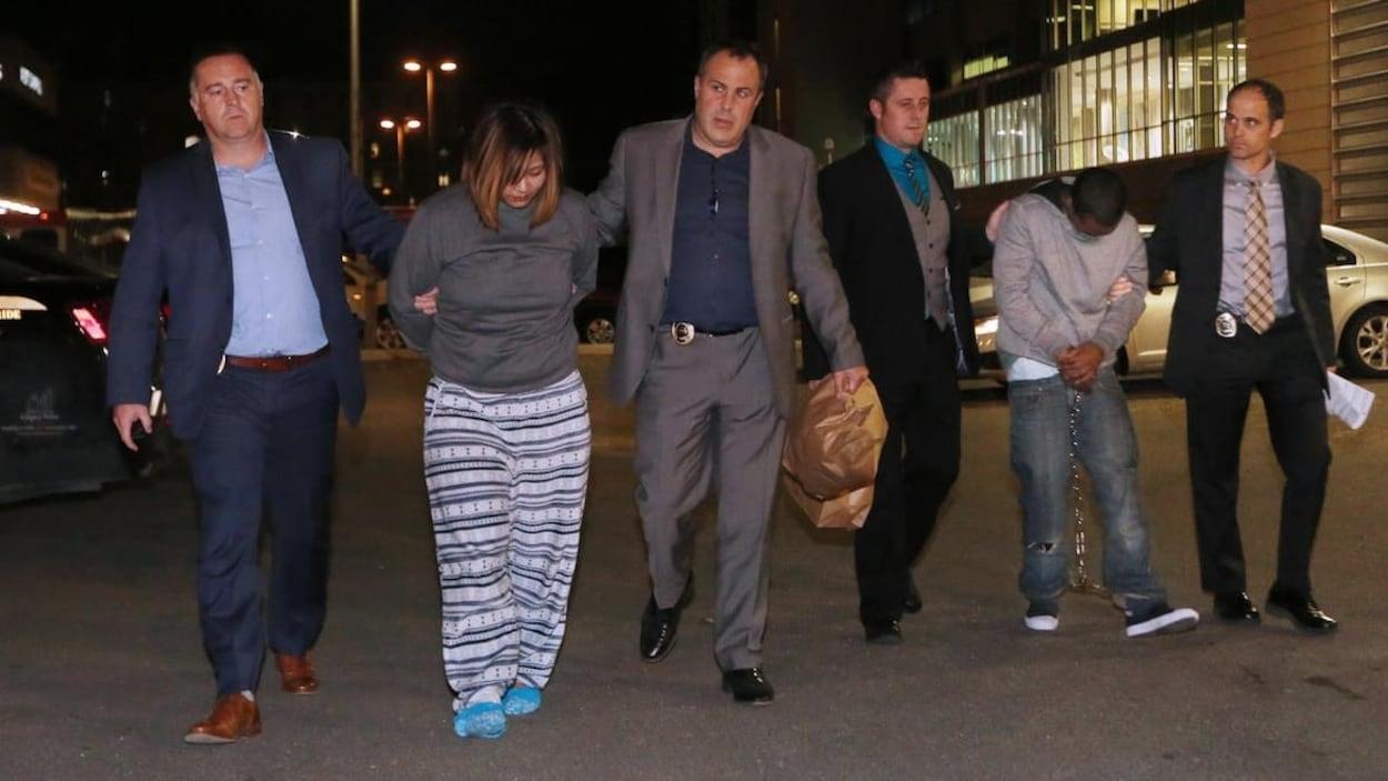 Une femme et un homme marchent tête baissée avec des menottes aux mains et aux pieds. Ils sont chacun encadrés par deux policiers. La scène se passe la nuit.