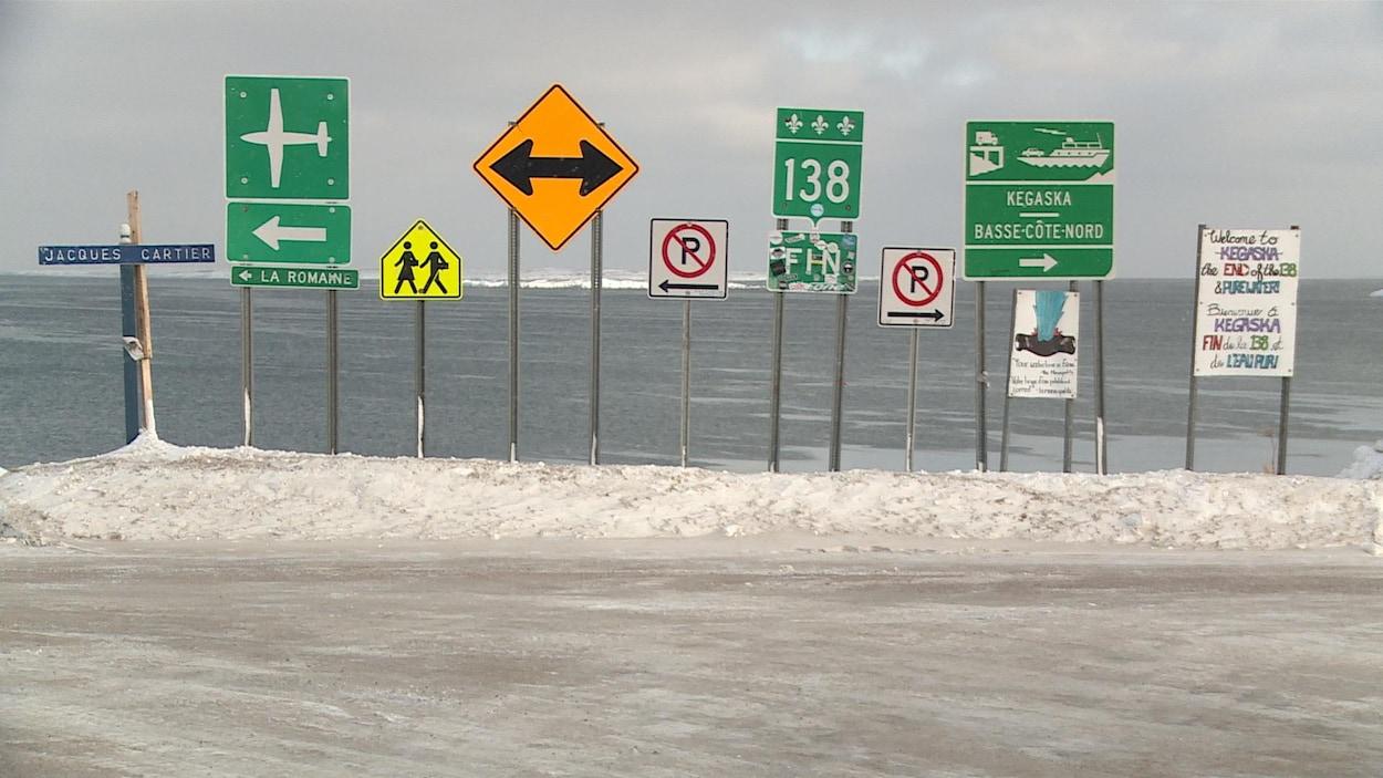 Panneaux annonçant la fin de la route 138 et les options de transport, par avion ou par bateau, pour continuer vers la Basse-Côte-Nord.