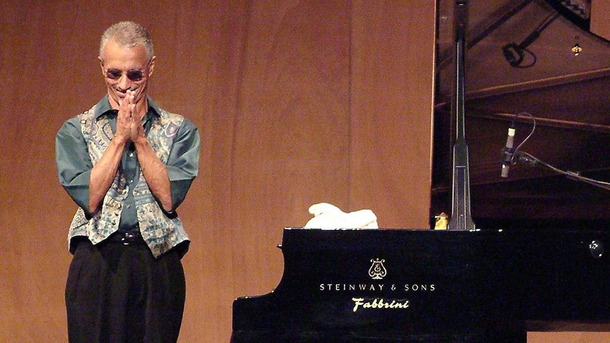 Le pianiste de jazz américain se tient debout sur scène, les mains jointes, près d'un piano de concert
