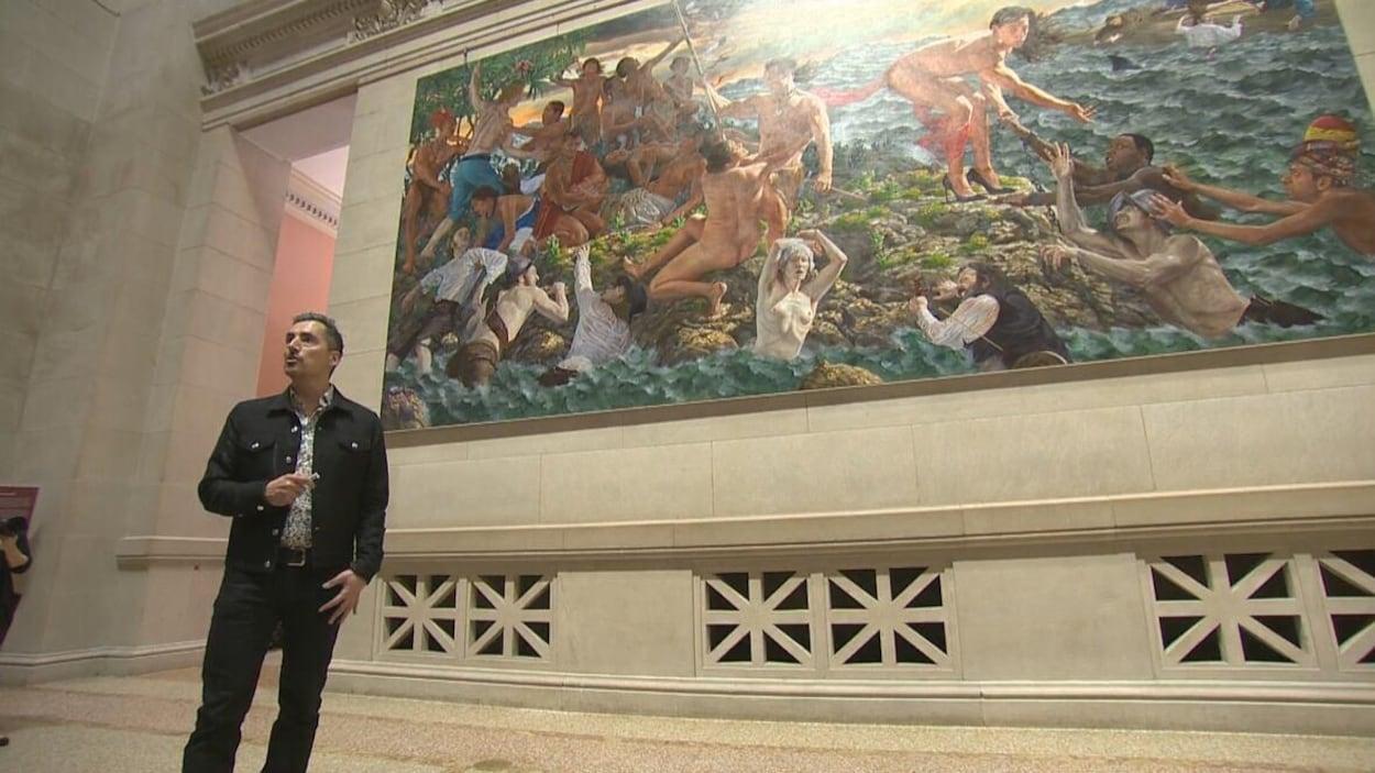 Kent Monkman parle, debout devant une de ses oeuvre.