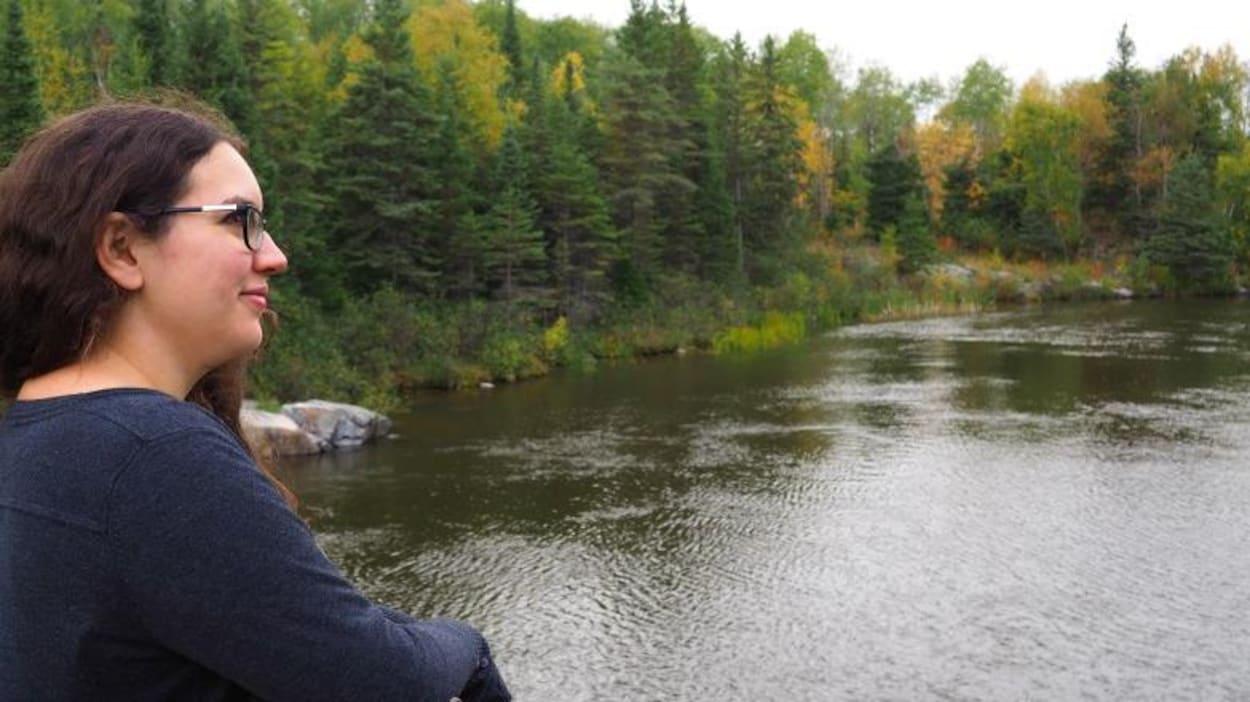 Une femme sur un pont suspendu au-dessus une rivière en pleine forêt regarde vers l'horizon.