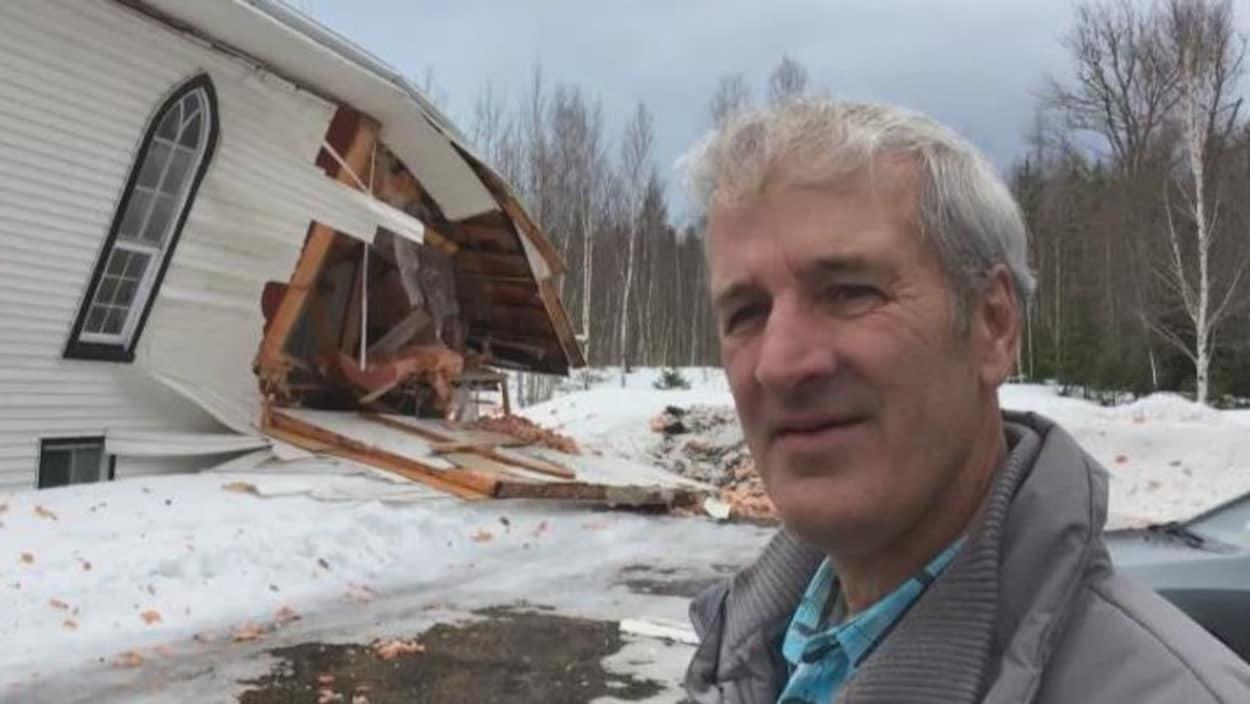 Portrait de Kevin Howe devant l'église partiellement détruite.