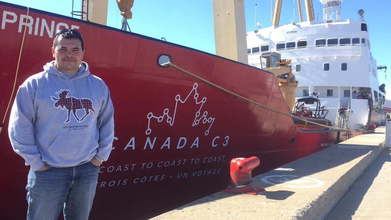 Kevin Laliberte devant le navire qui l'emmène le long du fleuve Saint-Laurent durant l'expédition C3.