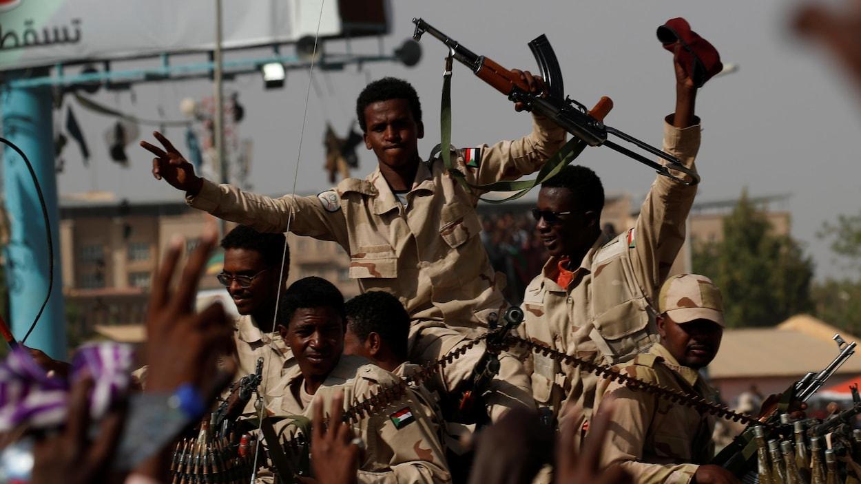 Cinq soldats soudanais se déplacent, les mains en l'air, avec des armes.